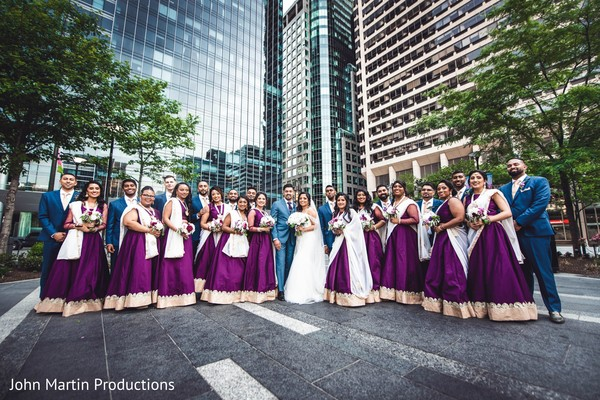 Indian couple posing outdoors with bridemaids and groosmen.