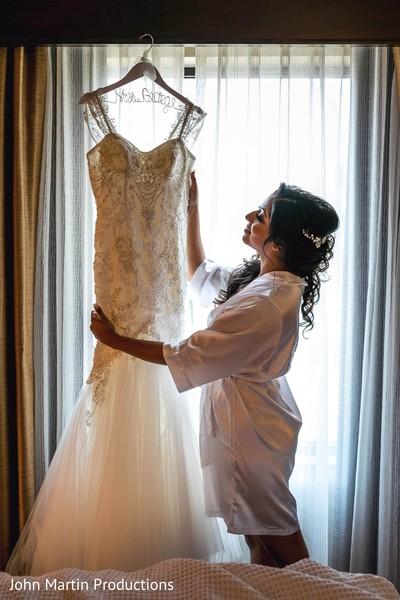 Indian bride admring her white wedding dress.