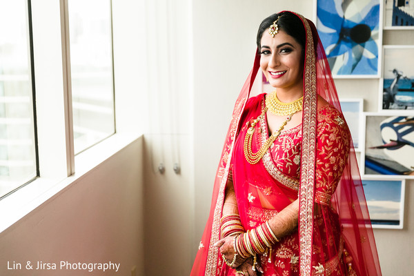 Indian bride in red and gold smiles for the camera