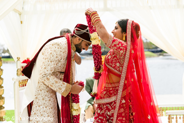 Indian bride putting a necklace on her Indian groom