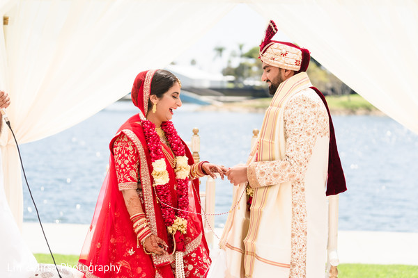 Indian groom putting the ring to bride.