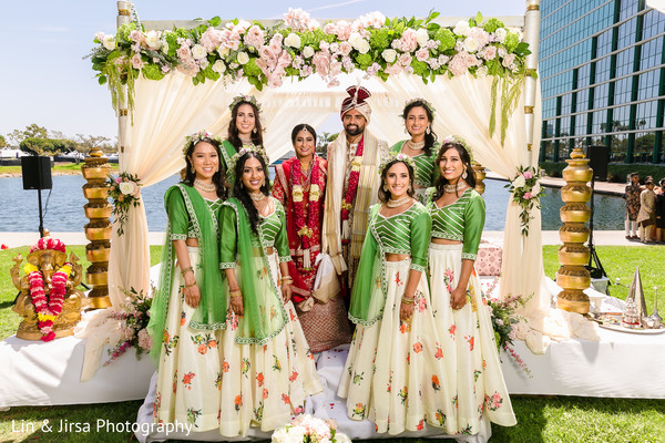 Indian couple posing with bridesmaids at ceremony mandap.