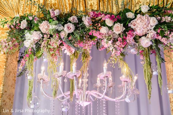 Indian wedding reception stage pink chandelier.