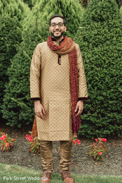 Indian groom wearing hies golden and red Dhoti Kurta.
