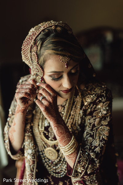Indian bride getting her gold earrings on.