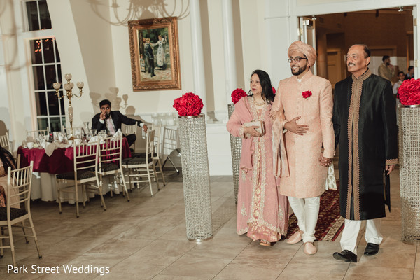 Indian groom entering wedding ceremony with relatives.