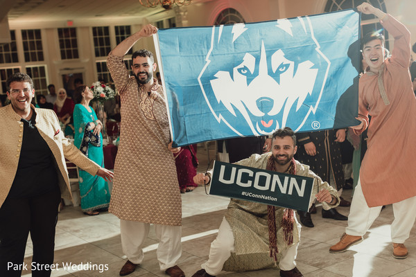 Indian groomsmen showing a University sign.