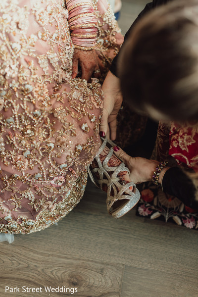 Indian bride putting on her reception silver high heels shoes.