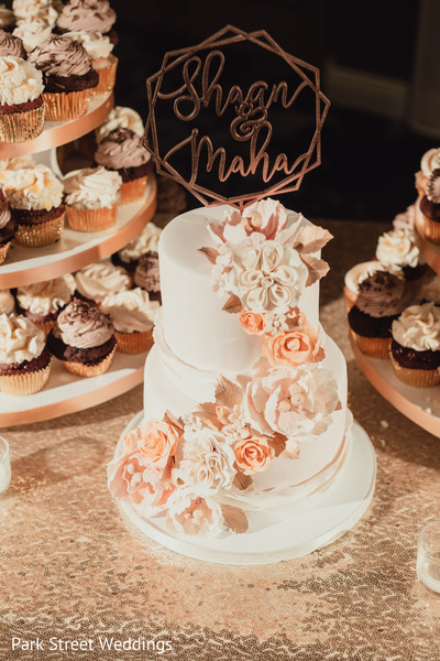 Cream and peach color Indian wedding cake decor.