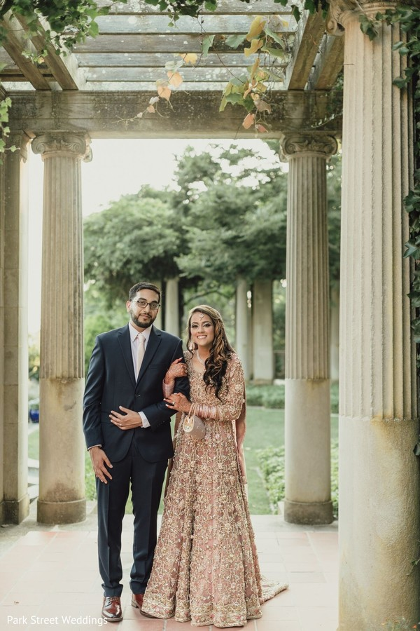 Indian bride on her pink Anarkali and groom on his black suit.