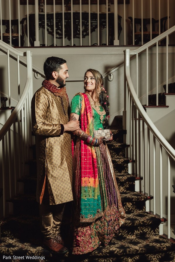 Indian couple posing on their golden, green and red sangeet outfits.