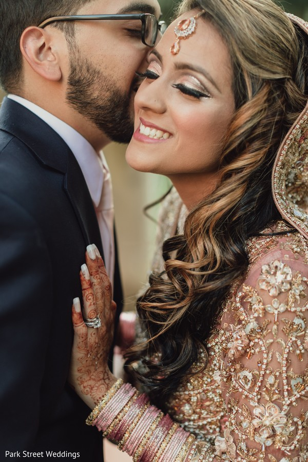 Indian groom giving a kiss to bride capture.