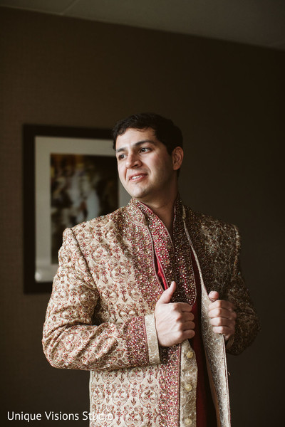 Indian groom adjusting his sherwani.