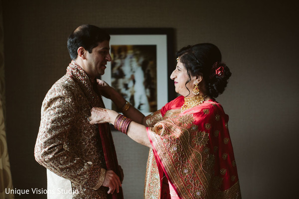 Indian groom being assisted with his scarf by a relative.