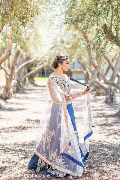 Indian birde oh her blue and golden ceremony lehenga.