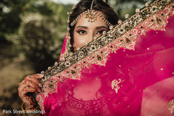 Indian bridal covering half-face with magenta veil