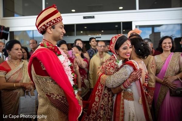 woman hugging Indian wedding couple