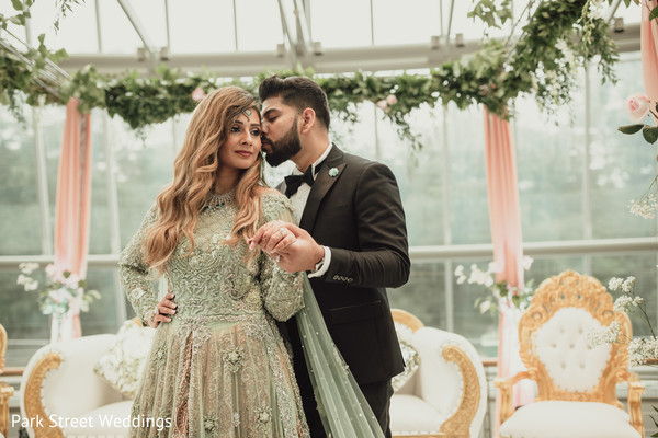 Indoor indian groom kissing bridal
