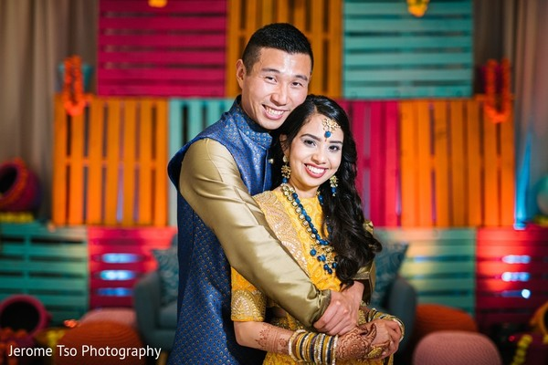 Indian bride and groom posing at sangeet stage.