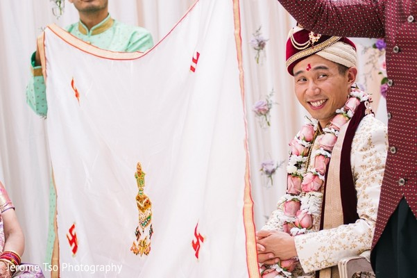Indian groom covered with white veil at wedding ceremony.