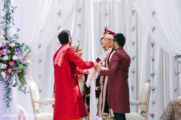 Indian bride and groom looking at each other at mandap.