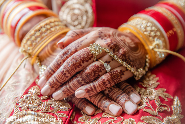 Indana bridal ceremony hands jewelry and henna decor.
