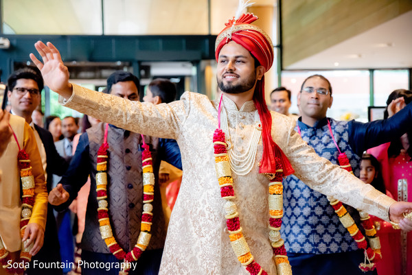 Indian groom on his ceremony red, white and golden outfit.