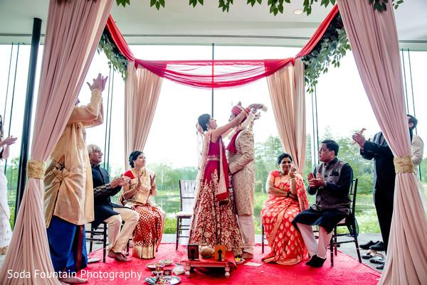 Indian bride and groom exchanging garlands ceremony.