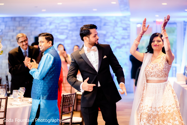 Indian couple dancing at reception entrance.