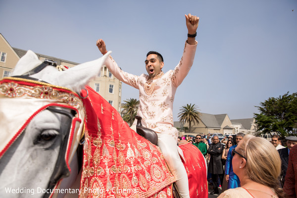 Indian groom riding white horse