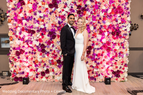 Indian couple posing on pink flowers reception stage.
