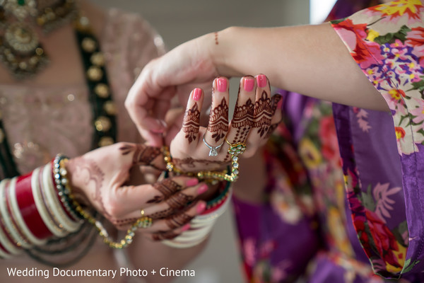 Indian bride putting on her yellow gold Hathphool.