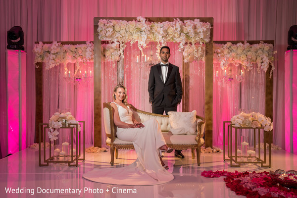 Indian bride and groom posing on reception pink stage.