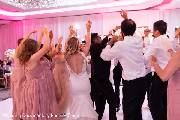 Indian couple dancing with bridesmaids and groomsmen capture.