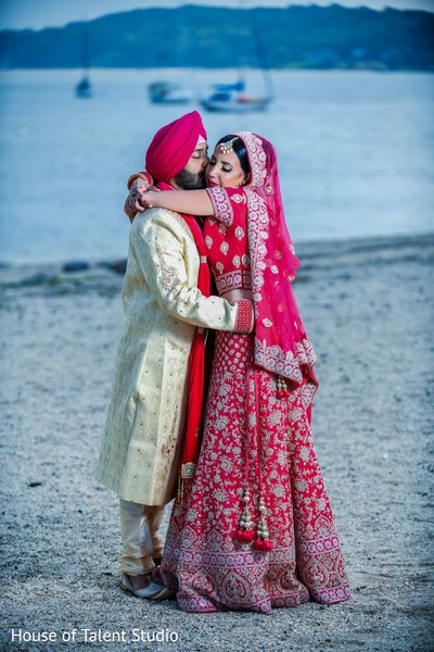 Indian couple embraces in front of the ocean