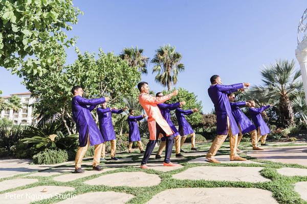 Indian groom dancing outdoors with groomsmen.