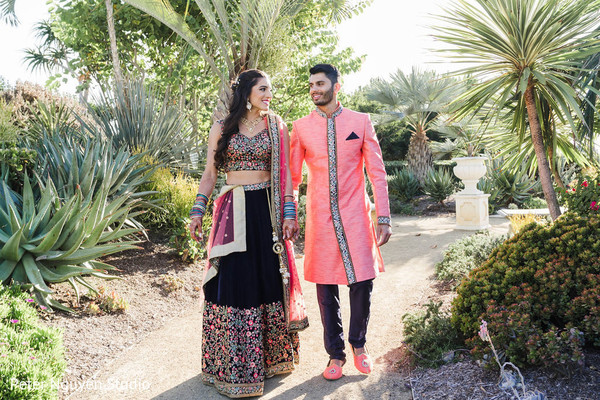 Indian couple walking outdoors holding hands.