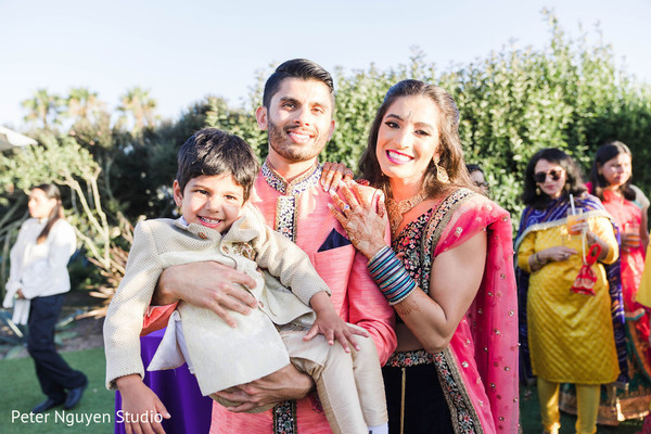 Indian bride and groom holding cute wedding guest.