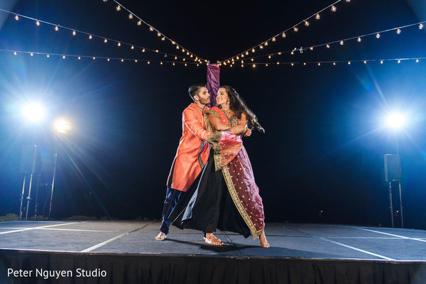 Indian bride and groom dancing at sangeet stage.