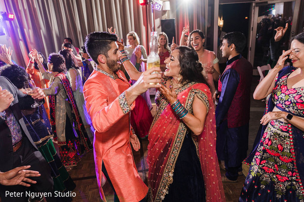 Indian couple dancing with guests at sangeet party.