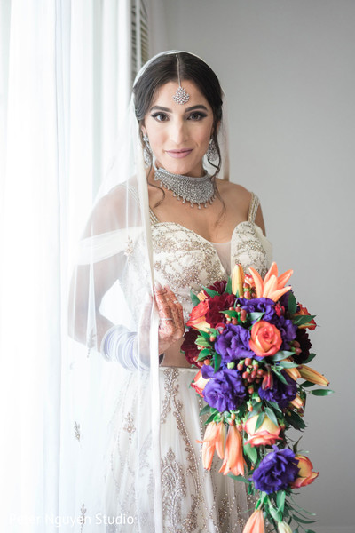 Maharani holding her coral and purple wedding bouquet.