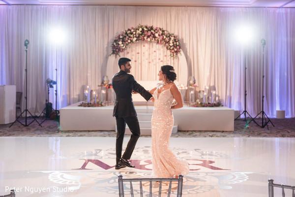 Indian couple dancing on monogrammed dance floor.
