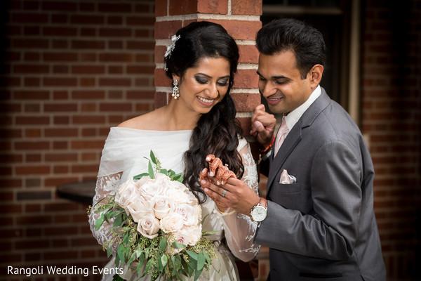 Indian groom admiring maharani's hand.