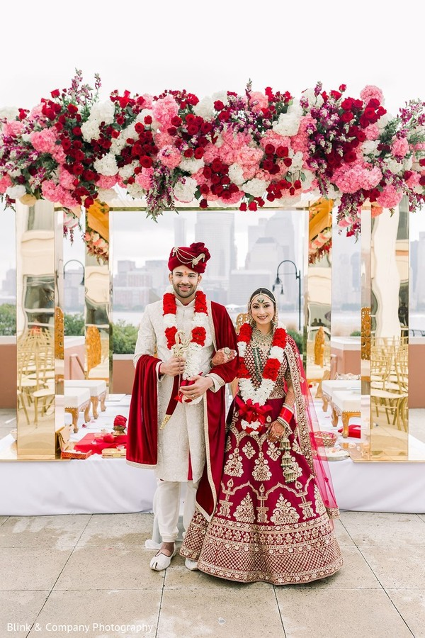 Indian couple posing in front of mandap.