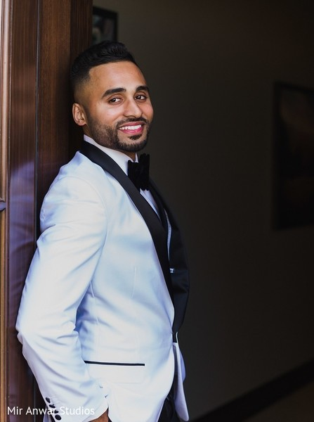 Indian groom on his white and black tuxedo.