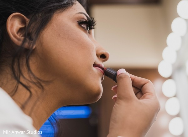 Indian bride getting her lipstick on .