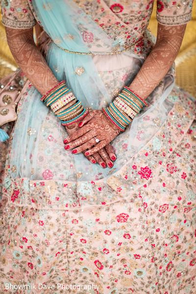 Fantastic Indian Bride posing her Mehndi art and bracelets.