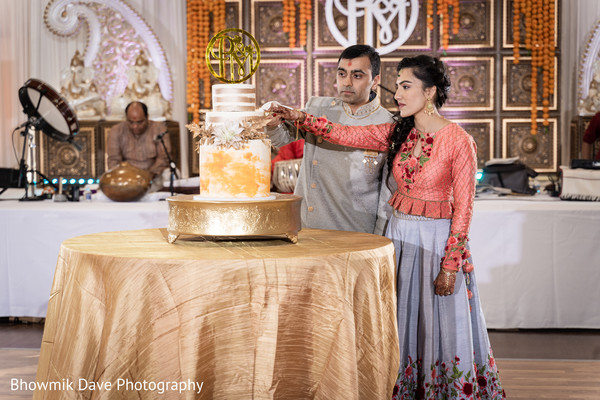 Indian bride and groom cutting their wedding cake.
