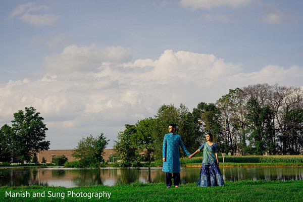 Indian couple holding hands near a pond