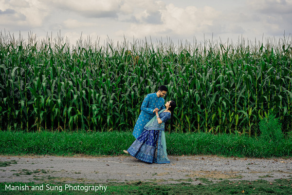 Indian couple dancing in front of a corn field
